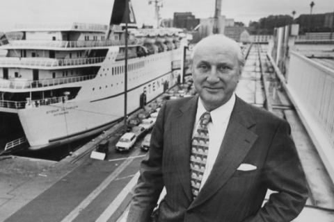 Black and white photo of a man in suit and tie in front of a Stena ferry