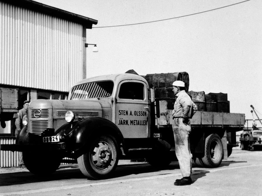 Historic black and white picture of man in front of truck