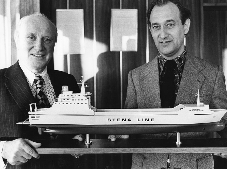 Two men holding a model of a ship